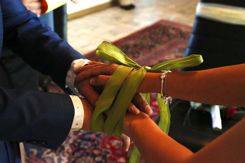 legare le mani degli sposi con un nastro verde
